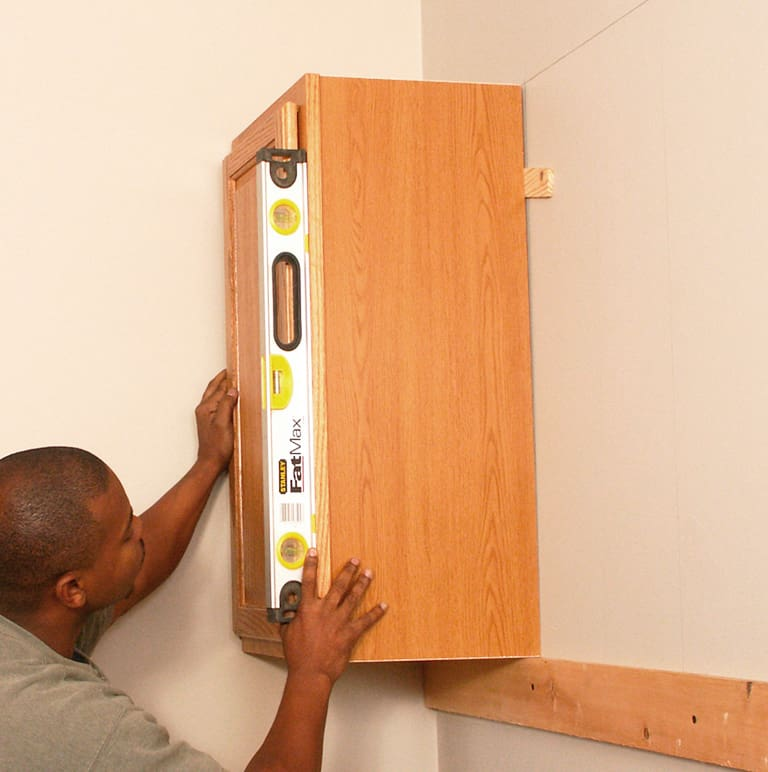 Support upper cabinets on a temporary rail. Then level and shim them before fastening them to wall studs.