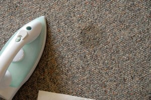 Use an iron and a paper towel to extract wax from carpet fibers.