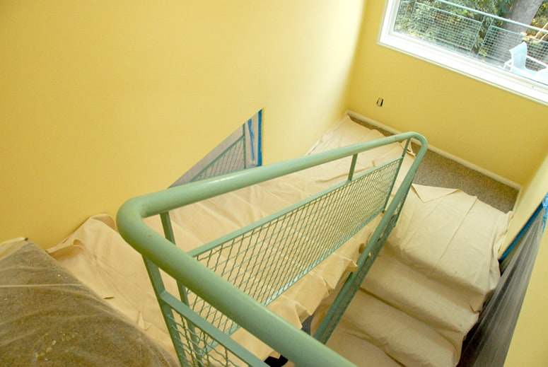 Use both plastic drop cloths and canvas drop cloths to protect carpeted areas and stairs during painting.