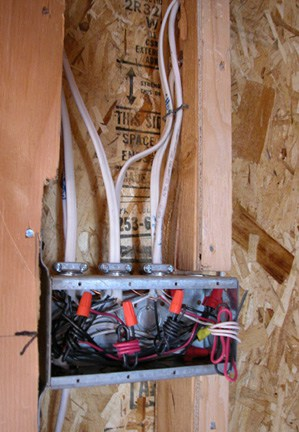 Nonmetallic cable is routed between wall studs; switches and receptacles fasten to electrical boxes.