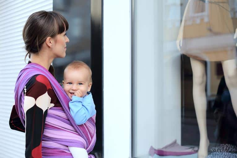 Sling-style baby carrier can be worn with baby either in front or back.