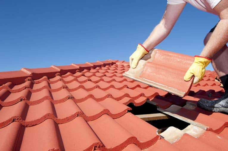Broken roof tile is pried out so that a new replacement can be slipped in beneath the course above it.