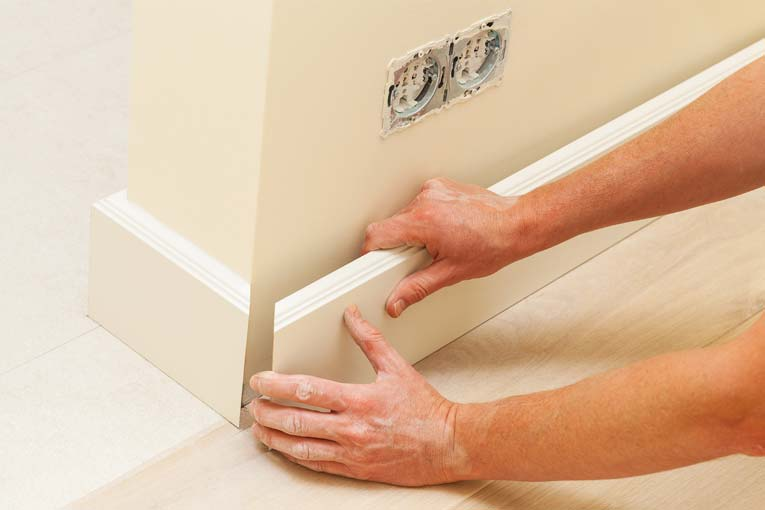Miter outside corners of base molding and check for fit before fastening in place.