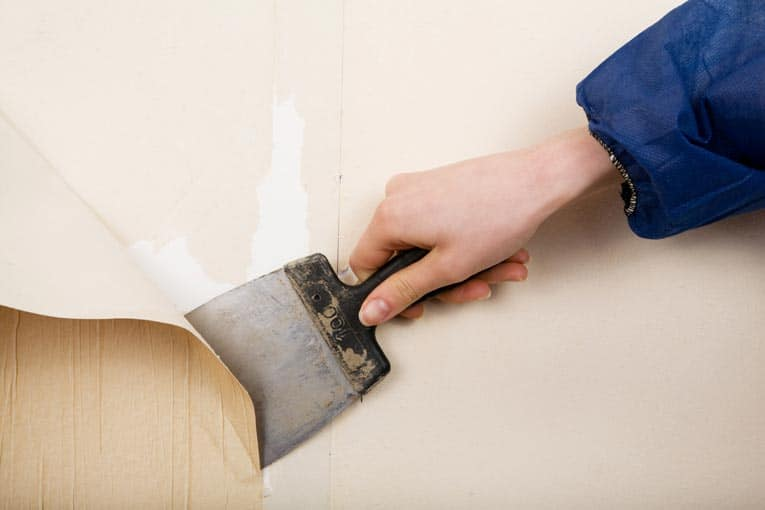 It's easy to remove old, loose wallpaper with a large putty knife.