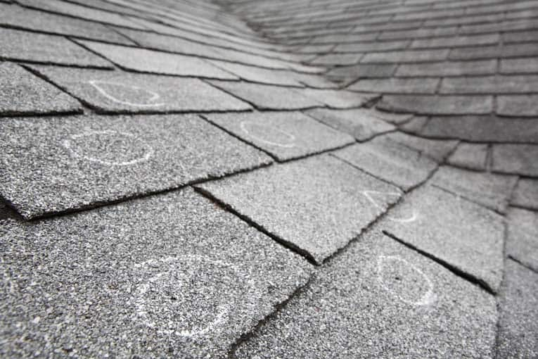 Asphalt roofing shingles requiring repair are marked on this roof. You can extend the life of a roof like this with basic repairs, but it ultimately will need to be replaced.