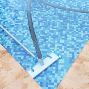 A pool vacuum has a hose that hooks up to the pool's intake. You guide it along the bottom and sides with an extension pole.
