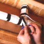 Man's hands connecting central vacuum wires on piping underneath the floor.