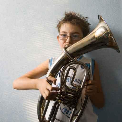 A boy blowing into a brass musical instrument.