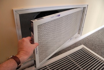 Man's hand removing an air conditioner filter on a wall return-air register.