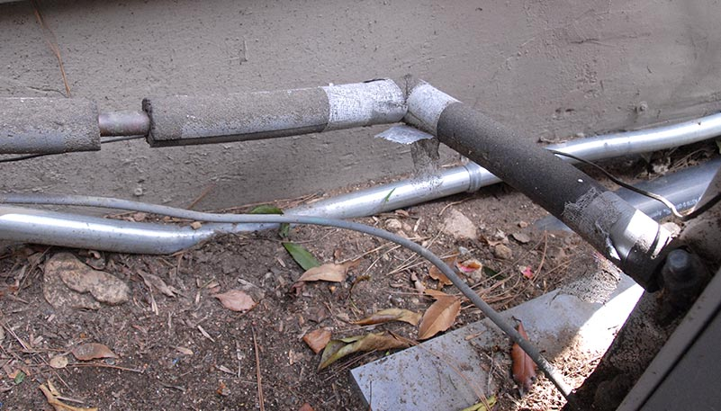 Outdoor coolant lines with missing sections of insulation.