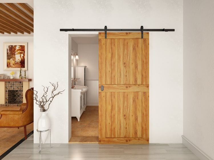 Wooden sliding barn door of a bathroom with a flat-track.