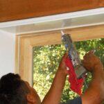 A man applying caulk on a window molding.