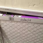 New replacement filter inserted, with date marks and arrows pointing to ductwork.