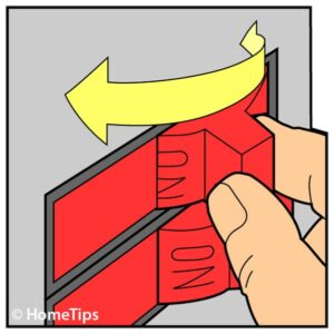 Man's fingers holding a red circuit breaker switch including an arrow pointing to a direction.