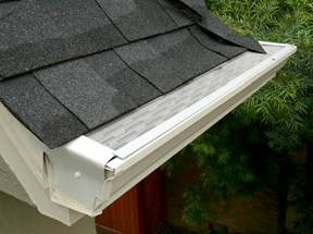 A micro-mesh gutter screen with aluminum frame on top of a house's white roof gutter.