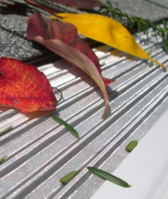 A stainless-steel, micro-mesh gutter screen in ribbed design, blocking the fallen leaves.