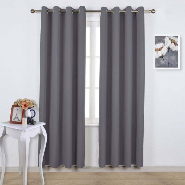 Noise reducing curtains hanging over windows in a bright room.