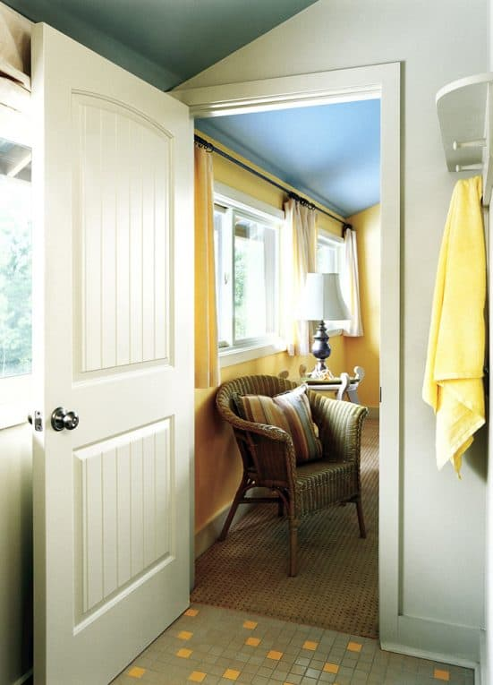 Wide-open white composite door, leading from a bathroom into a bedroom.