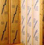 Kraft-faced insulation batts between studs of a corner interior wall.