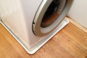 Plastic tray below the front-loading washing machine.