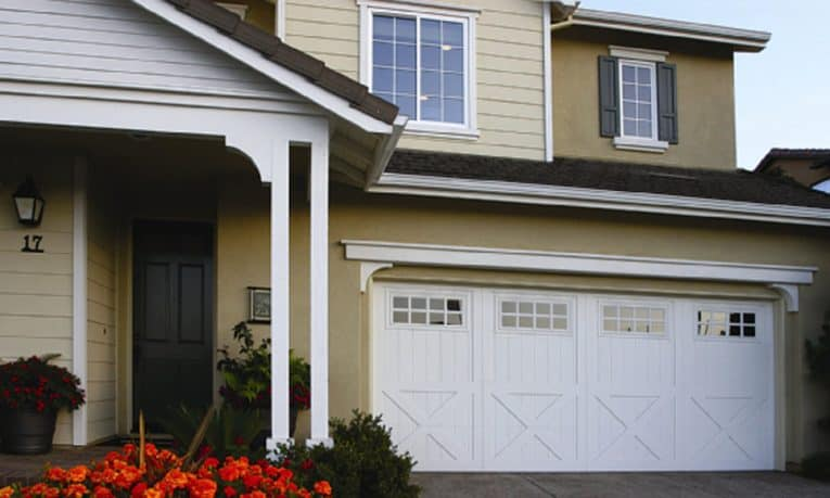 Two-story bungalow house's front yard including some flowers and a large carriage-style, white wooden door garage.