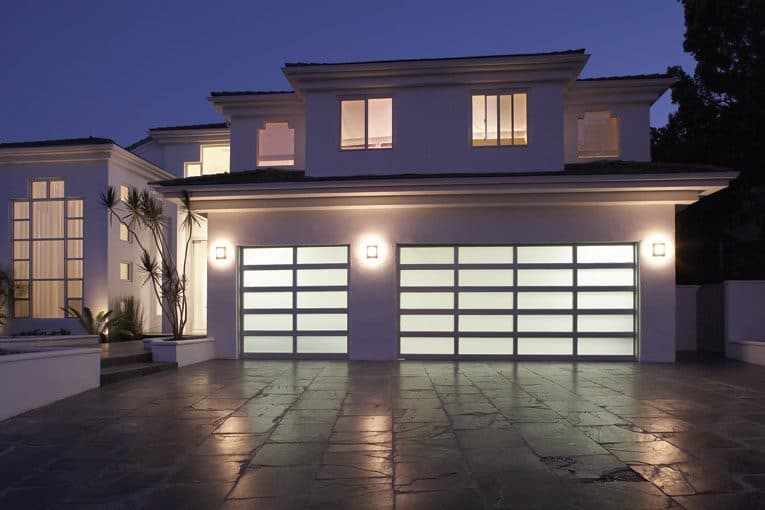 Two-story modern house's front yard including outdoor lighting and a bright translucent, aluminum-framed, double door garage.