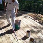 Man cleaning a wood deck, using a paint roller with an extension pole.