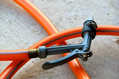 High-pressure garden hose nozzle hand sprayer control laid on a floor.