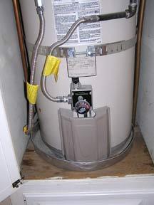 A water heater drip pan installed beneath a storage water heater.