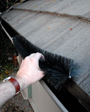 Man's hand taking out a black, long brush from a gutter.