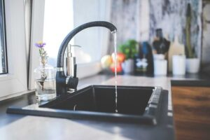 A black kitchen faucet with water running.