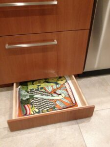Toe-kick drawer offers flat storage for potholders, placemats, and more.