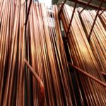 Rigid copper pipes in varying thicknesses arranged vertically.