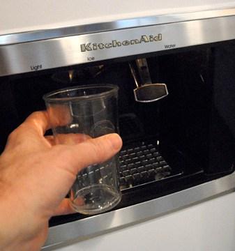 Hand holding a glass under an ice maker.