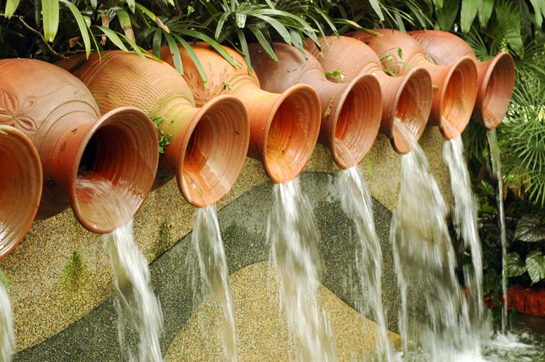A series of ceramic pots spill water into this pond, creating a stunning waterfall.