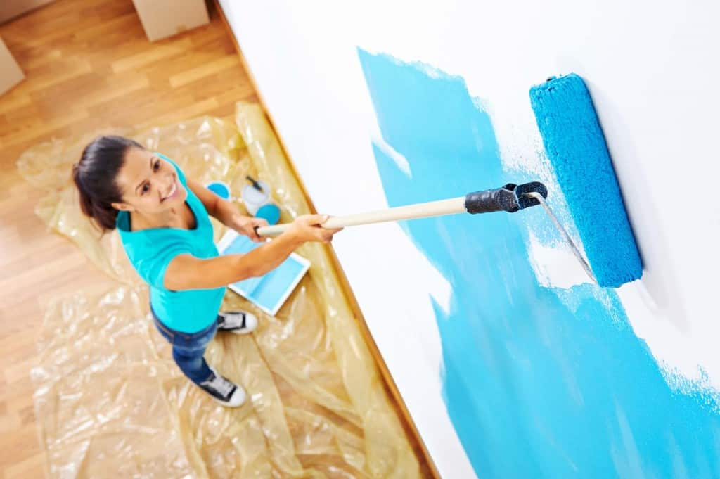 Woman painting a wall using a roller attached to an extension pole.