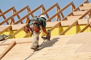 Man nailing plywood sheathing to roof rafters.