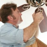 A man assembling a ceiling fan on the ceiling using a screwdriver.