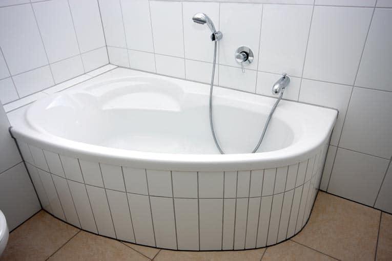 Small corner bathtub is designed to squeeze into a corner in a small bathroom.