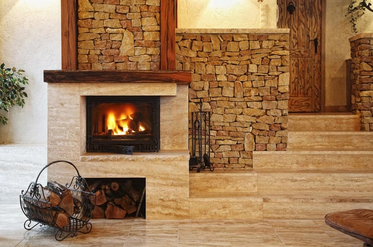 Stylish wood-burning stone fireplace provides a central focal point in this contemporary living room.