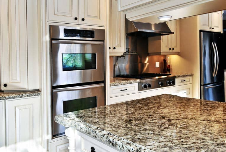 Built-in double ovens are complimented by a drop-in gas range.