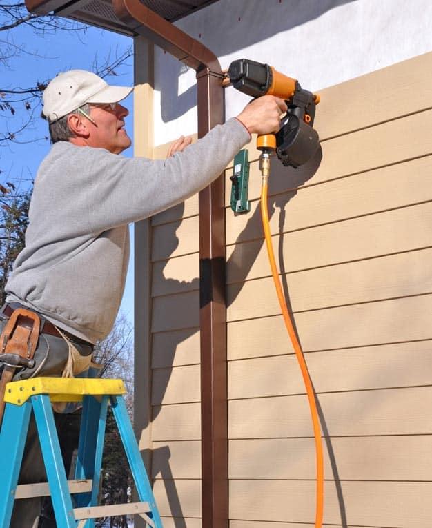 Man installing a fiber-cement wall siding with a nail gun.