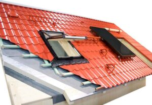 Cut-away diagram of a red metal roofing with insulation including internal and external parts, a skylight, and a solar panel.