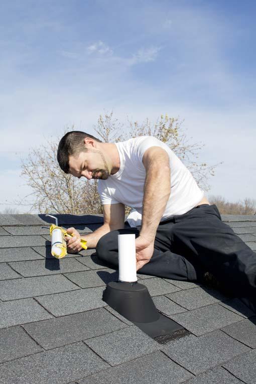 Man sealing a roof vent pipe flashing using a caulk gun.
