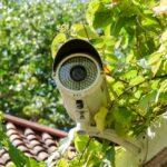 A white bullet-type, outdoor home surveillance camera.