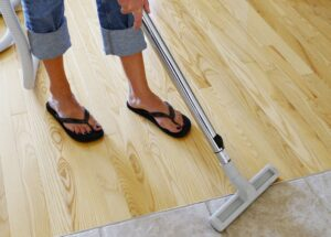 Woman vacuuming around a wooden and tiled floor.