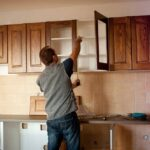 man measuring for cabinet refacing