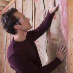 man installing fiberglass insulation between wall studs