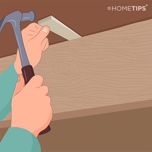 Hands hammering a wood wedge between the subfloor and a joist to prevent squeaking.