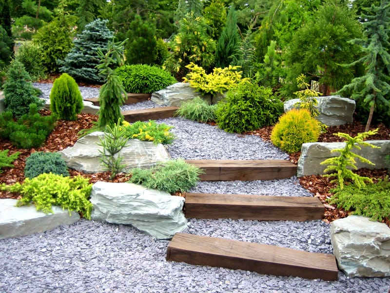A gently rising pathway of gravel, with large wood beam steps.